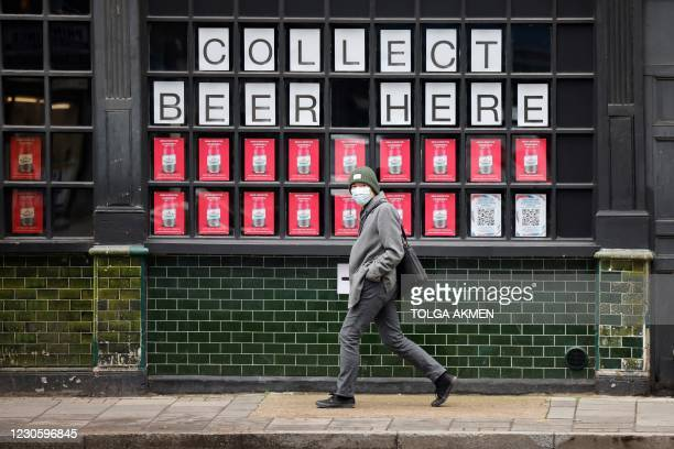 Man wearing a face mask as a precautionary measure against COVID-19, walks past a closed pub in the City of London, on January 15 during the third...