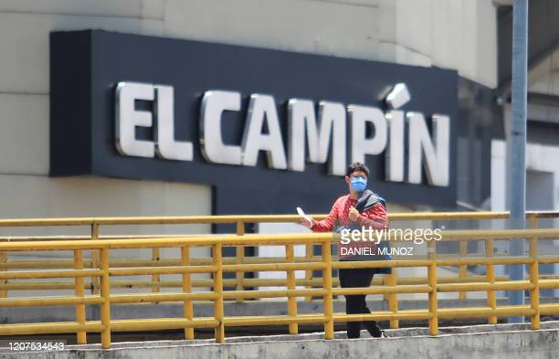 Man wearing a face mask as a precautionary measure against the spread of the new coronavirus, COVID-19, walks outside El Campin stadium in Bogota on...