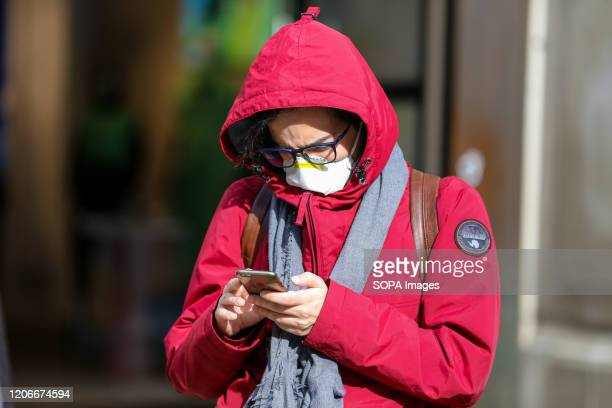 A man wearing a face mask as a preventive measure against the corona virus views his mobile phone in central London 8 people have died from the virus...