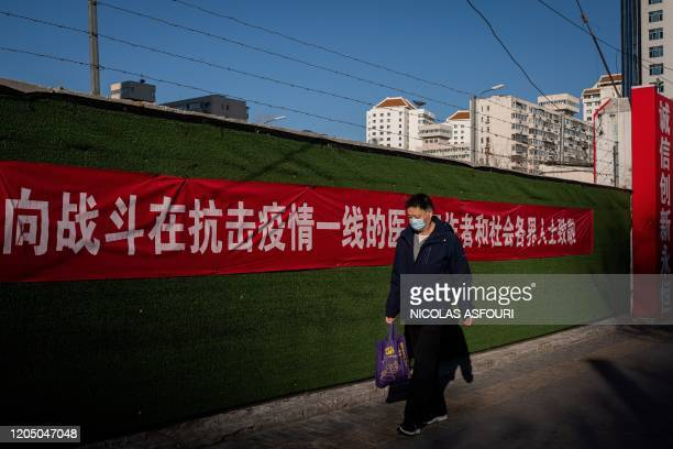"Man wearing a face mask as a preventive measure against the COVID-19 coronavirus walk on a street past a government banner that reads ""Fight against..."