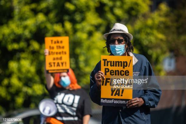 A man wearing a face mask as a preventive measure against the spread of COVID19 holds a sign during an antiTrump protest where demonstrators...