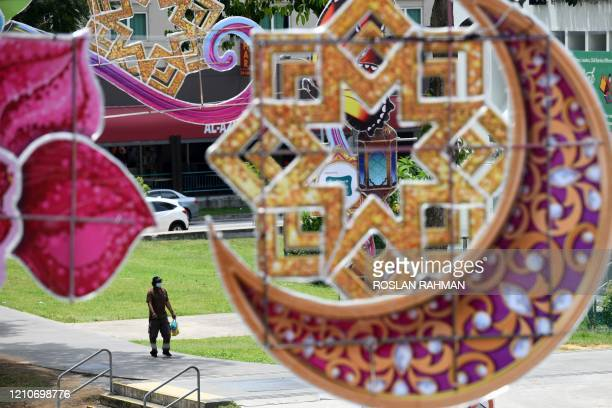 Man, wearing a face mask as a preventive measure against the spread of the COVID-19 novel coronavirus, walks past decorations for the holy Muslim...
