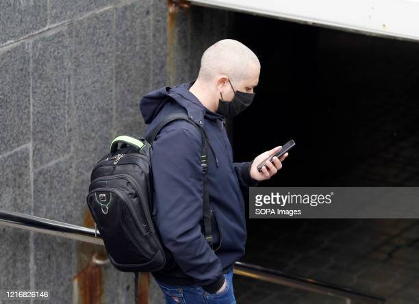 A man wearing a face mask as a preventive measure against the spread of coronavirus uses his a mobile phone on a street in downtown Kiev Ukraine's...