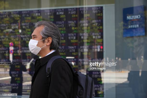 Man wearing a face mask as a preventive measure against the spread of Covid-19 stands in front of an electronic board showing Japans Nikkei 225 index...
