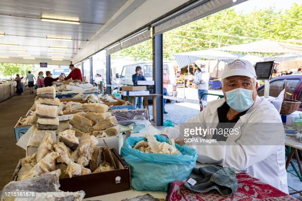 A man wearing a face mask as a preventive measure waits for customers at the Portuguese codfish bank on the first day of the fair in Espinho amid...