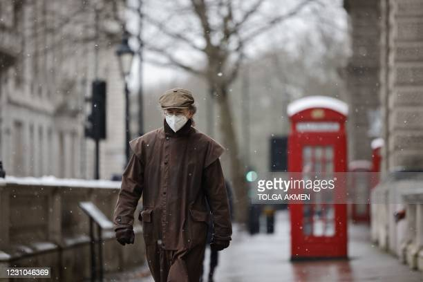 Man wearing a face mask because of the coronavirus pandemic walks in the street in London on February 8, 2021.