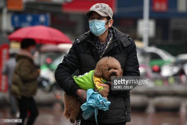 A man wearing a face mask carries his pet dog along a street in Jiujiang in China's central Jiangxi province on March 6 2020 China reported 30 more...