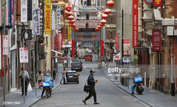 Man wearing a face mask crosses a quiet road in Melbourne's Chinatown area on August 13, 2020. - Australia's virus-hit Victoria state reported a...