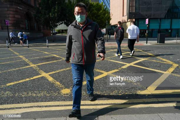 A man wearing a face mask crosses a road in Newcastle on September 17 2020 in Newcastle upon Tyne England Almost two million people in northeast...