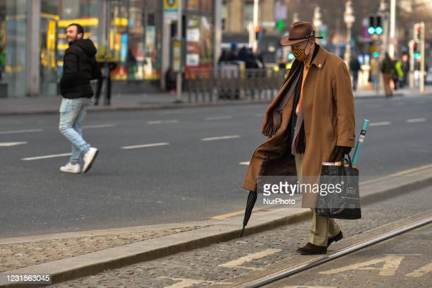 Man wearing a face mask crosses the street in Dublin city center during Level 5 Covid-19 lockdown. On Saturday, 6 March in Dublin, Ireland.