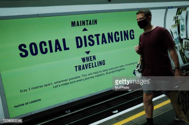 A man wearing a face mask currently mandated on public transport passes a poster reminding passengers of the need for social distancing on a Northern...