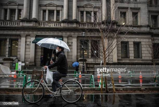 A man wearing a face mask cycles past the Bank of Japan in Tokyo's financial district on March 2 2020 in Tokyo Japan Prime Minister Shinzo Abe...