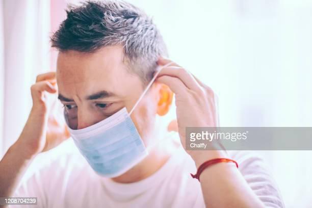 homme utilisant un masque de visage pendant l'éclosion de coronavirus - masque de chirurgien photos et images de collection