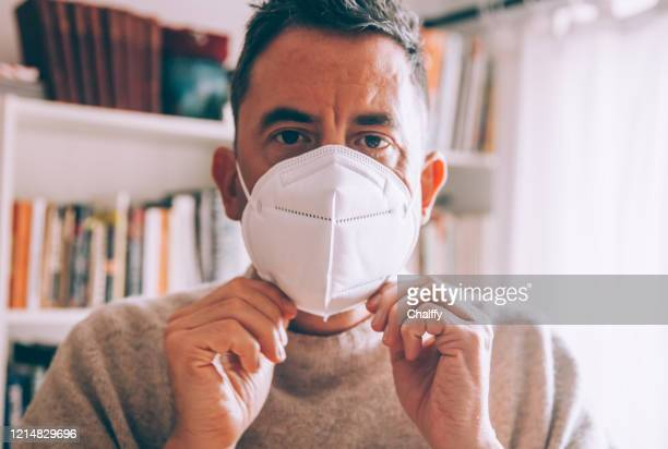 man wearing a face mask during coronavirus outbreak - stay at home order stock pictures, royalty-free photos & images