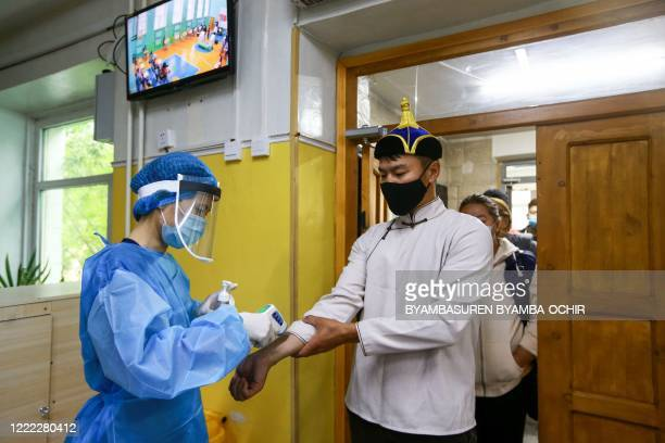 Man wearing a face mask has his body temperature checked as he arrives to vote at a polling station in Ulaanbaatar, the capital of Mongolia on June...