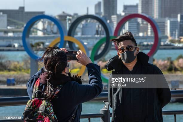 Man wearing a face mask has his photograph taken in front of the Olympic Rings in Odaiba on March 5, 2020 in Tokyo, Japan. An increasing number of...