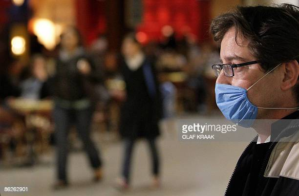 Man wearing a face mask helping in the prevention from infection of swine flu is pictured after his arrival from Mexico at Amsterdam Schiphol...