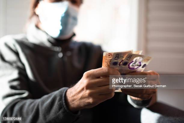 a man wearing a face mask, holding five and ten pound notes - currency stock pictures, royalty-free photos & images