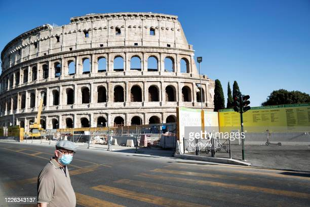 Man wearing a face mask in front of the Colosseo on July 10 2020 in Roma, Italy.