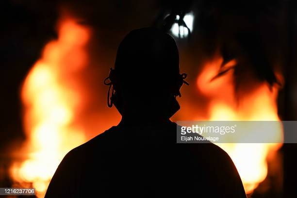 A man wearing a face mask is seen silhouetted in front of a burning police car during a protest on May 29 2020 in Atlanta Georgia Demonstrations are...