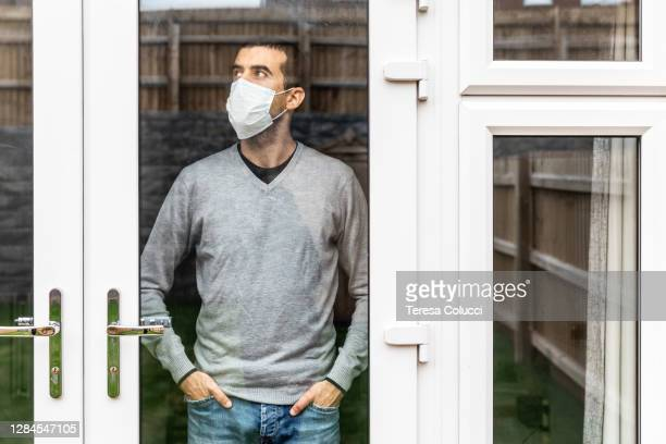 man wearing a face mask isolating at home and looking out of the window - lockdown stock pictures, royalty-free photos & images