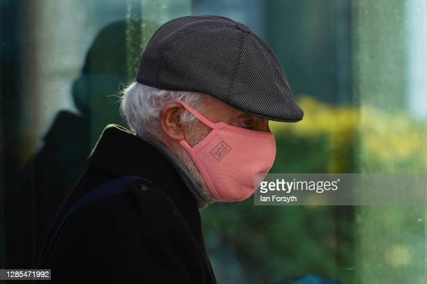 Man wearing a face mask leaves a coffee shop in Hull city centre on November 13, 2020 in Hull, England. Hull recorded 726.8 new cases per 100,000...