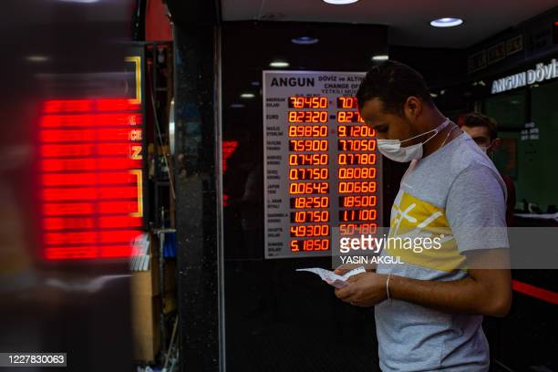 Man wearing a face mask leaves after changing money at an exchange office in Istanbul, on July 29, 2020. - According to reports, the Turkish Lira...