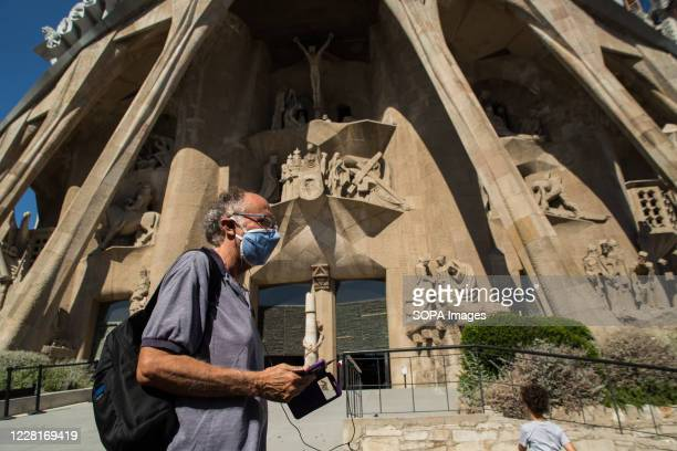 Man wearing a face mask, listens to an audio guide of the Sagrada Familia tour. Barcelona residents visit La Sagrada Familia following strict...