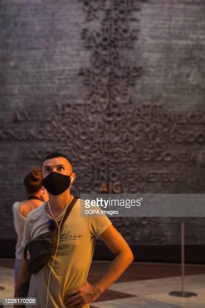 Man wearing a face mask, listens to an audio guide of the Sagrada Familia. Barcelona residents visit La Sagrada Familia following strict Coronavirus...
