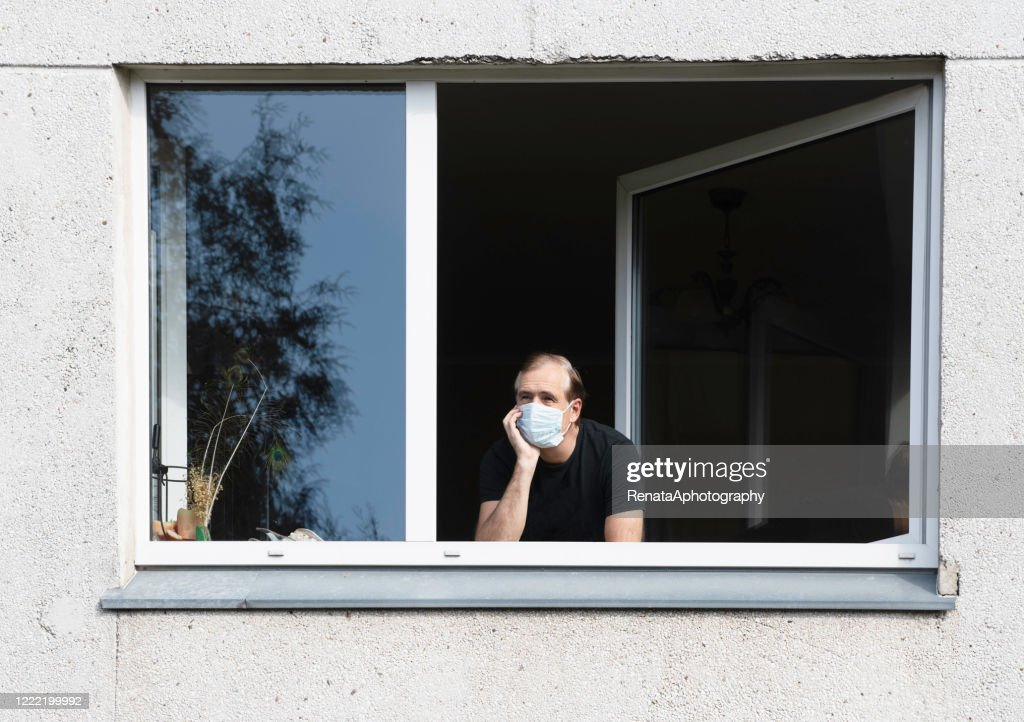 Man wearing a face mask looking out of a window, Lithuania : Stock Photo