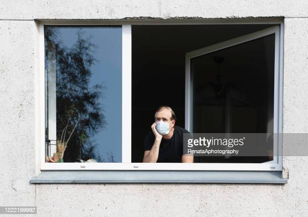 man wearing a face mask looking out of a window, lithuania - ロックダウン ストックフォトと画像
