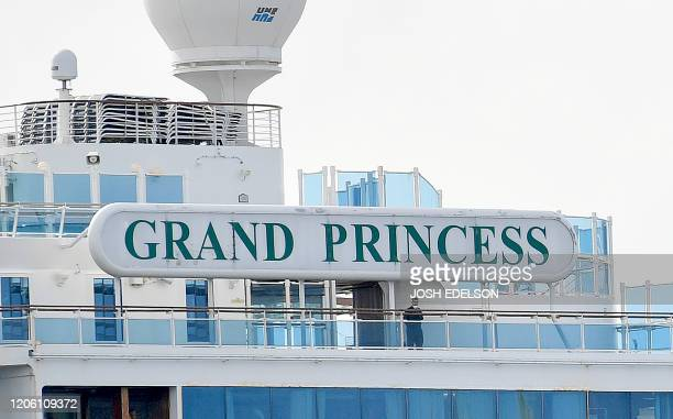 A man wearing a face mask looks out from aboard the Grand Princess cruise ship operated by Princess Cruises as it maintains a holding pattern about...