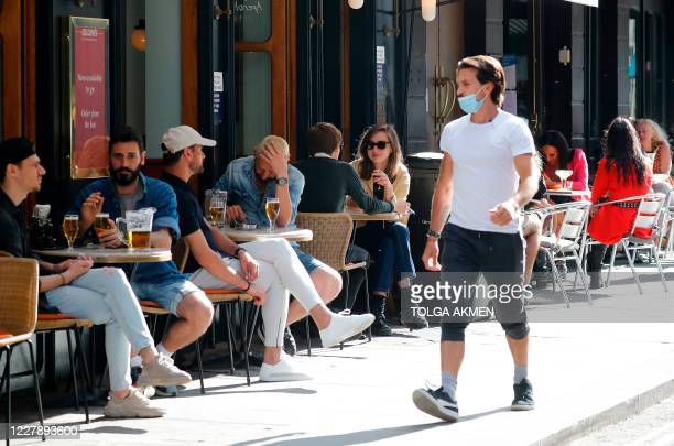 Man wearing a face mask or covering due to the COVID-19 pandemic, walks past consumers sat outside a restaurant in London on August 3 as the...