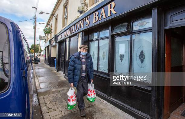 Man wearing a face mask or covering due to the COVID-19 pandemic, walks past the closed Donelon's Bar in the rural village of Dunmore, west of...