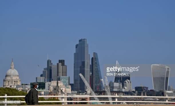 Man wearing a face mask or covering due to the COVID-19 pandemic, walks across Waterloo Bridge, backdropped by the skyscrapers of the City of London,...
