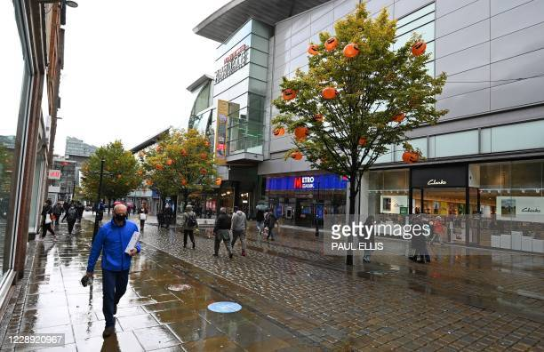 Man wearing a face mask or covering due to the COVID-19 pandemic, walks past a tree decorated in pumpkins ahead of Halloween, in Manchester, northern...