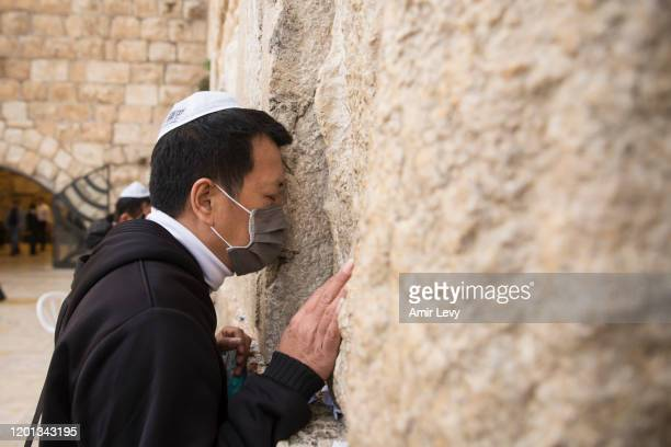 Man wearing a face mask prays during a mass prayer at the Western Wall for coronavirus patients in Jerusalem's Old City on February 16, 2020 in...