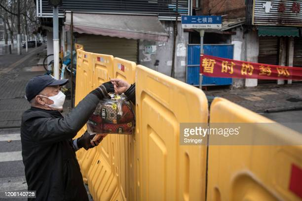 Man wearing a face mask receives a package through a makeshift barricade wall built to control entry and exit to a residential compound on March 8,...
