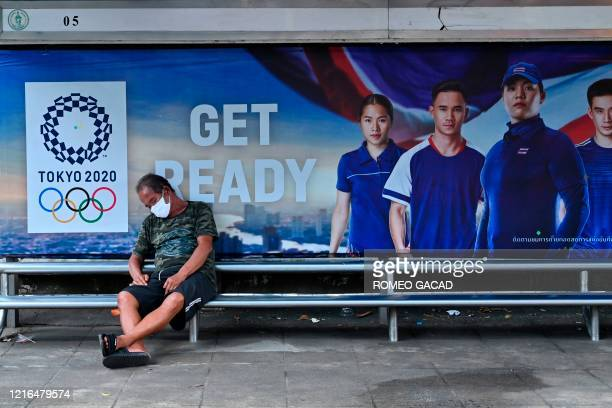 A man wearing a face mask rests at a bus stop with a poster display of Thai athletes for the Tokyo 2020 Olympic Games in Bangkok on May 31 2020