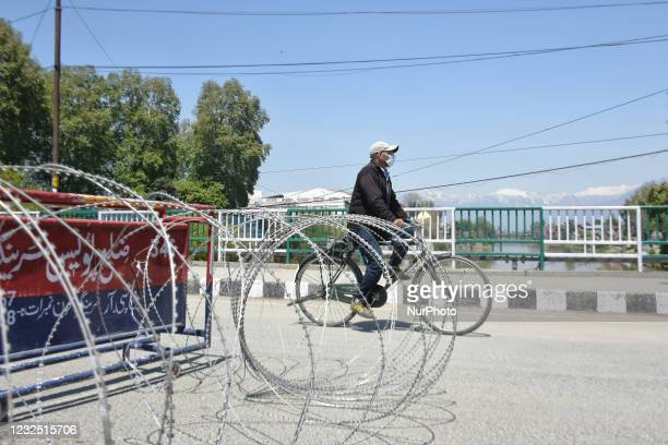 Man wearing a face mask rides his bicycle on a deserted street during Covid-19 curfew in Srinagar, indian Administered Kashmir on 25 April 2021....