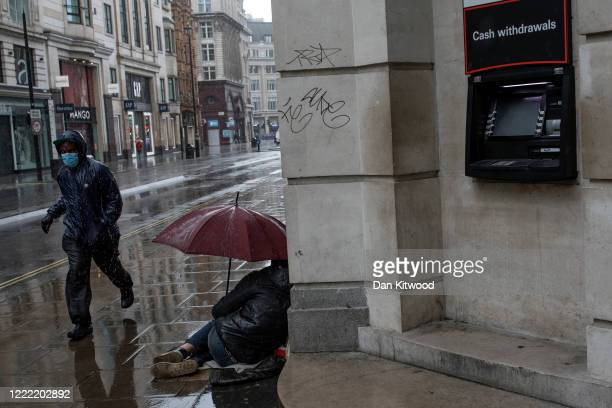 Man wearing a face mask runs through the rain past a homeless man on Oxford Street on May 01, 2020 in London, England. British Prime Minister Boris...