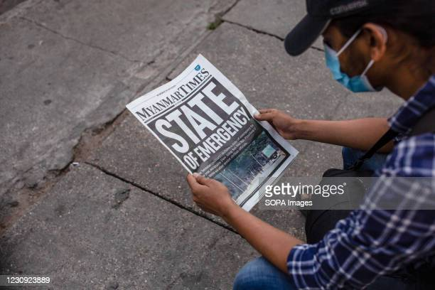 Man wearing a face mask seen reading a the Myanmar Times newspaper with the headline 'State of Emergency' a day after the Myanmar's military detained...