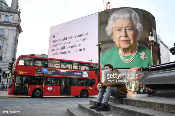 Man wearing a face mask sits in front of an image of Queen Elizabeth II and quotes from her broadcast to the nation in relation to the coronavirus...