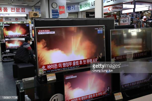 Man wearing a face mask sits near TV screens showing a news program reporting about North Korea's missiles with file images at an electronic shop on...