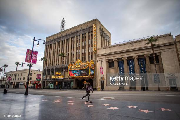 Man wearing a face mask skateboards past the El Capitan theatre down the Hollywood Walk of Fame in Hollywood on April 19 amid the novel coronavirus...