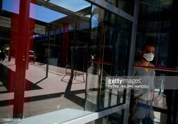 A man wearing a face mask stands at the entrance of the Ifema convention and exhibition centre in Madrid on April 03 2020 where a temporary hospital...
