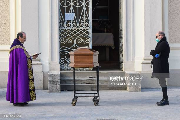 A man wearing a face mask stands by the coffin of his mother as a priest reads prayers during a funeral service in the closed cemetery of Seriate...