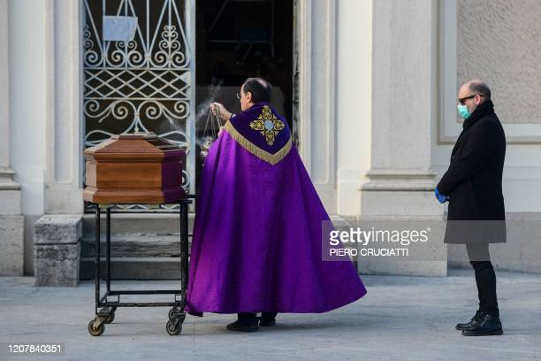 A man wearing a face mask stands by the coffin of his mother as a priest swings a thurible of incense during a funeral service in the closed cemetery...