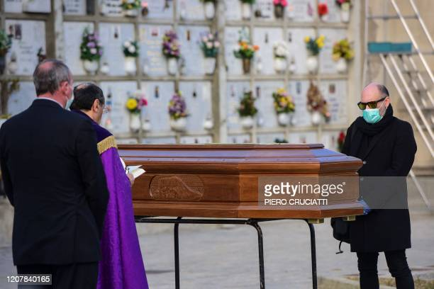 A man wearing a face mask stands by the coffin of his mother during a funeral service in the closed cemetery of Seriate near Bergamo Lombardy on...