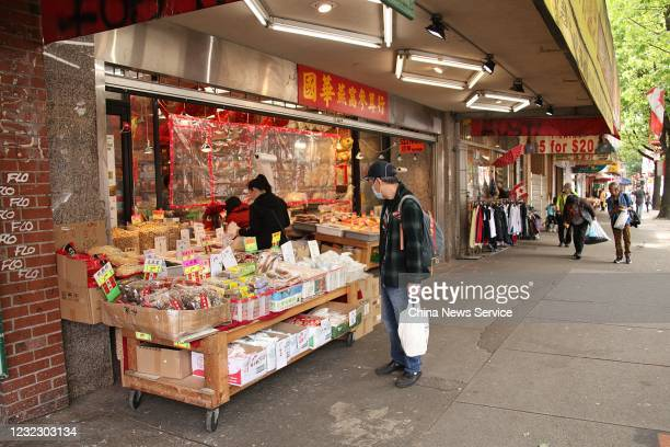 A man wearing a face mask stands in front of a store at Chinatown on May 28 2020 in Vancouver Canada The Coronavirus pandemic has spread to many...